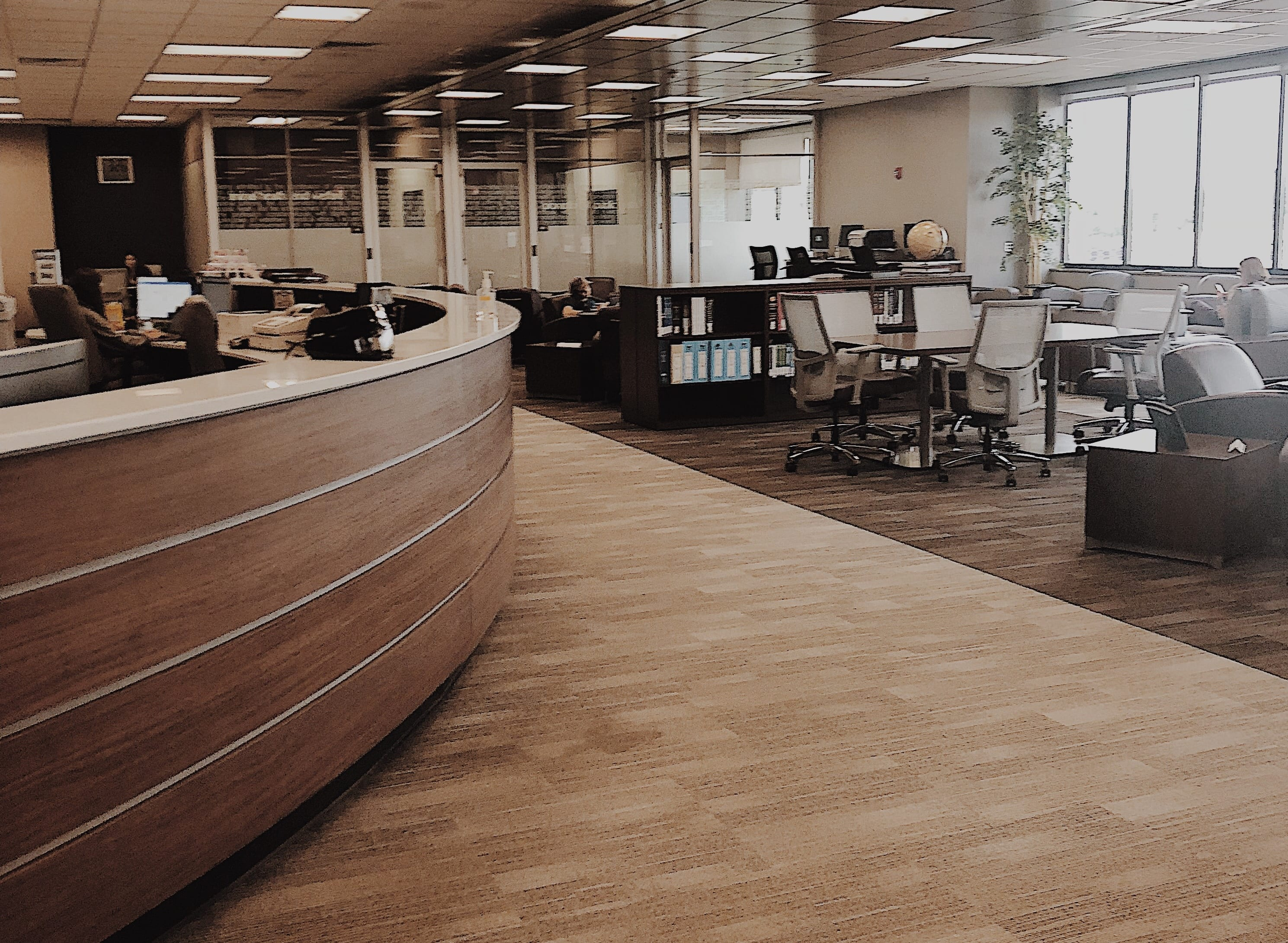 A curved help desk at the left is adjacent to a study area with tables and office chairs, as well a variety of soft seating.