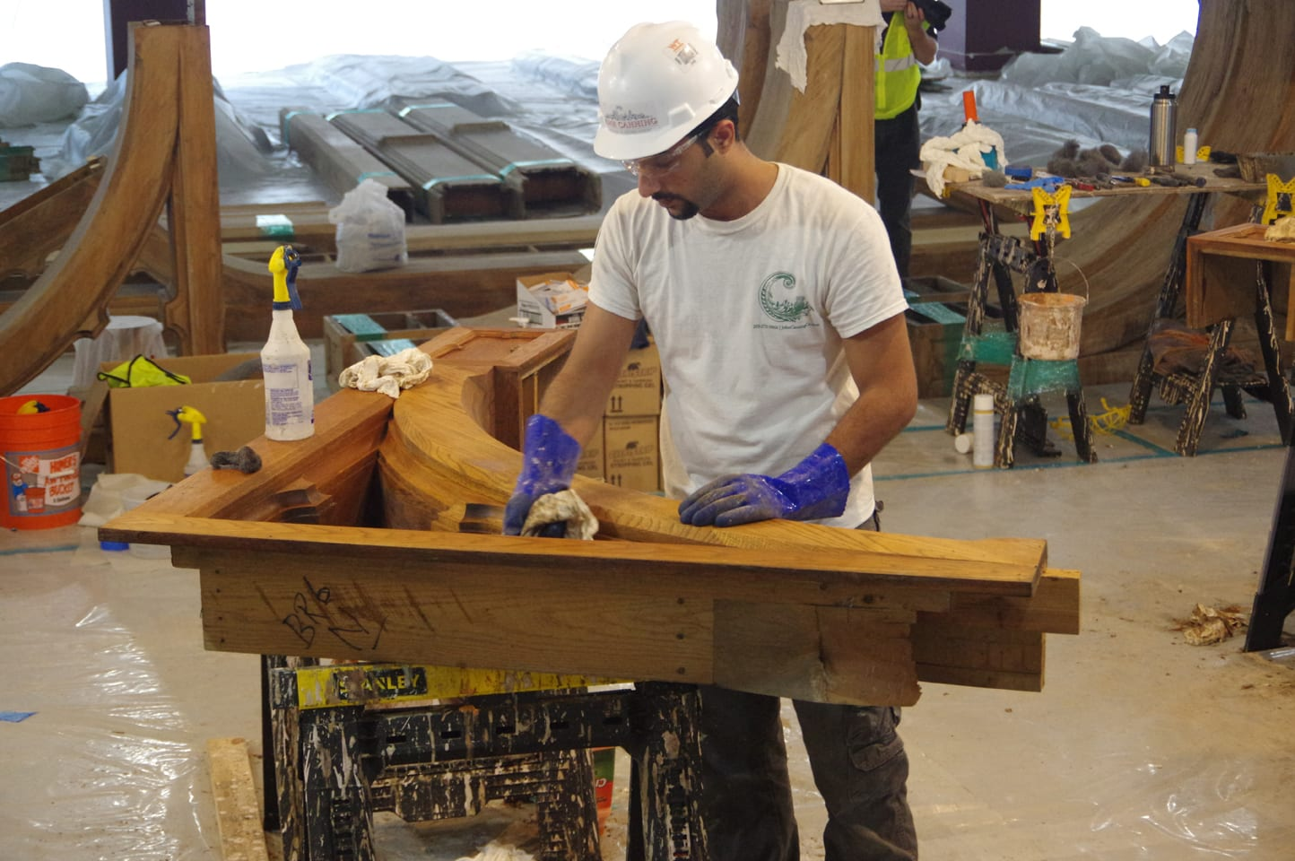 A dark-haired man in a white t-shirt and hardhat uses a cloth to wipe a heavy piece of wood sitting on sawhorses.