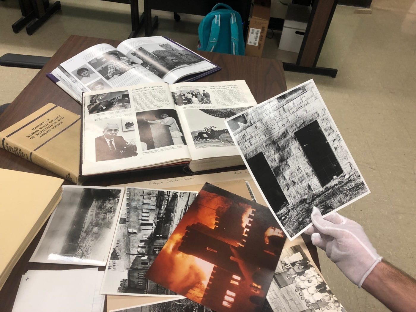 Multiple open books and large photographs in both color and black and white are spread across a long table.