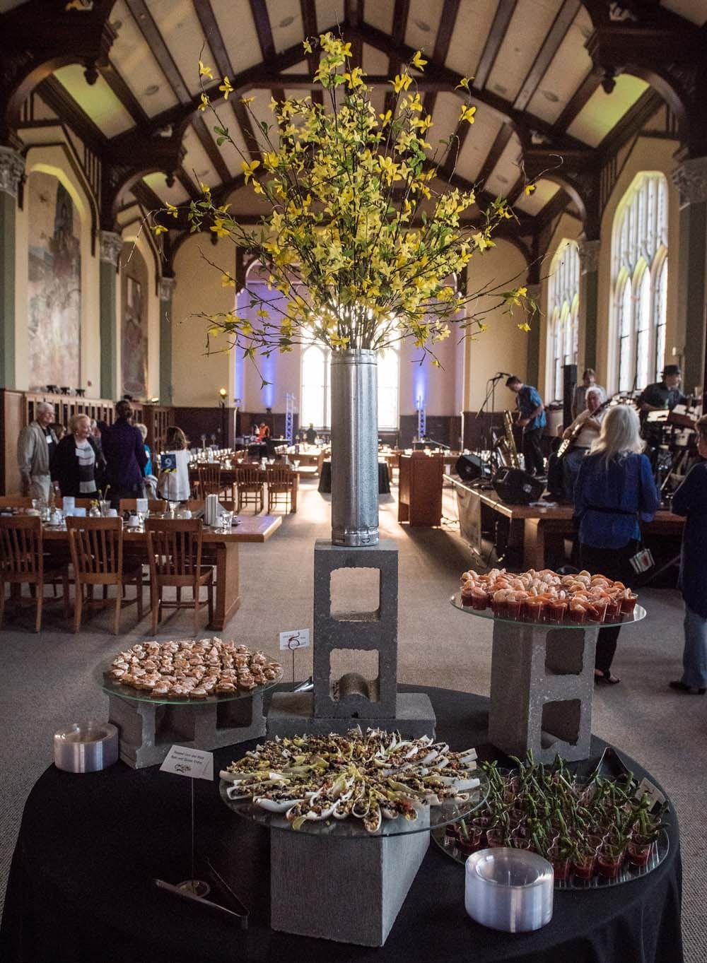 A table in the Great Room decorated with construction materials like cement blocks holds a large bouquet of yellow forsythia and trays of hors d'oeuvres.