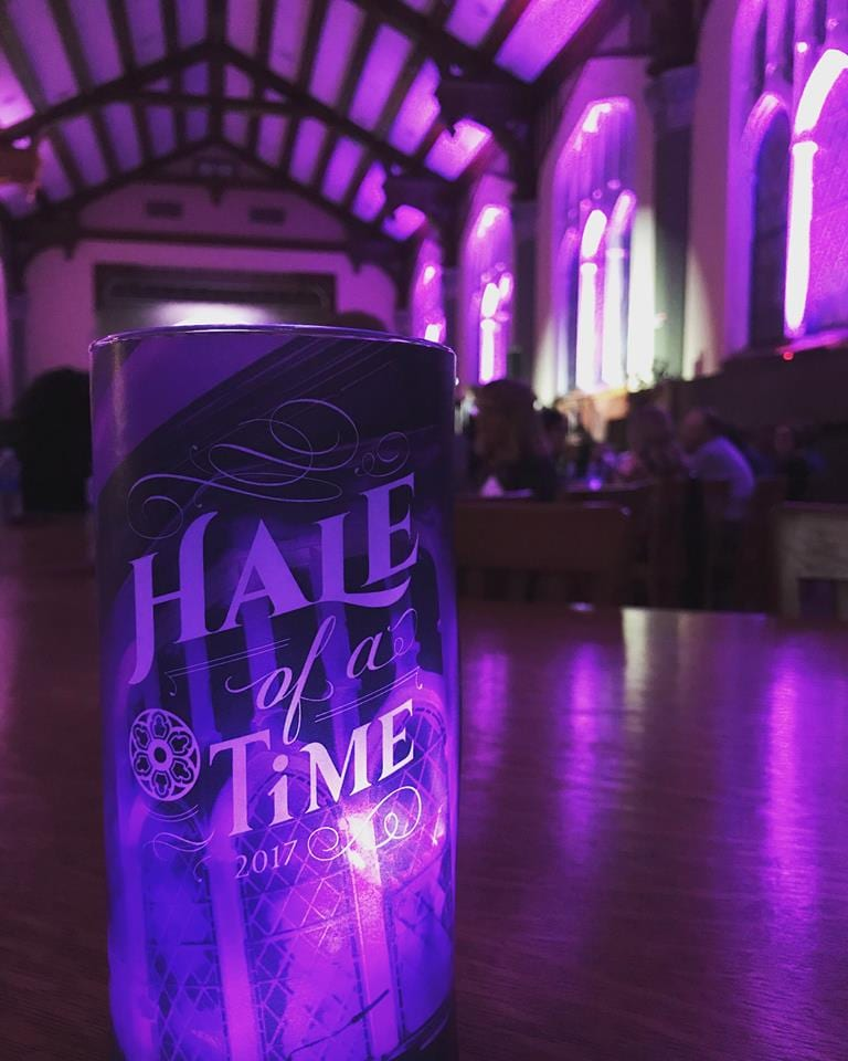 "A purple candle emblazoned with text that says ""Hale of a Time"" stands on a table in the Great Room, which is lit up with purple lights."