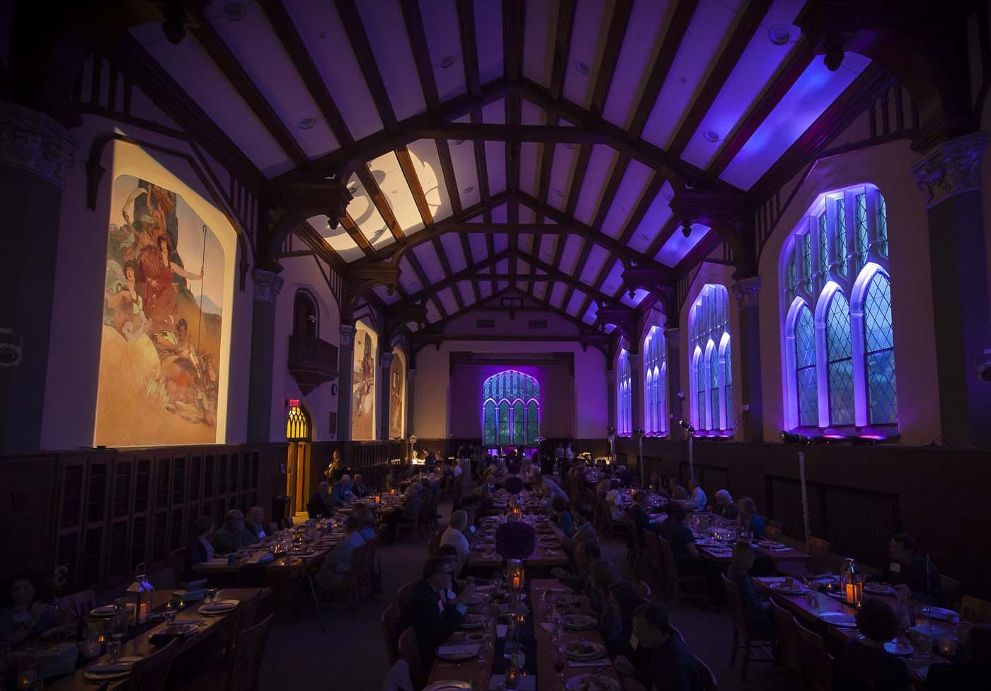The Great Room is filled with tables of gala guests and washed in purple lights. Spotlights highlight the art deco murals along one wall.