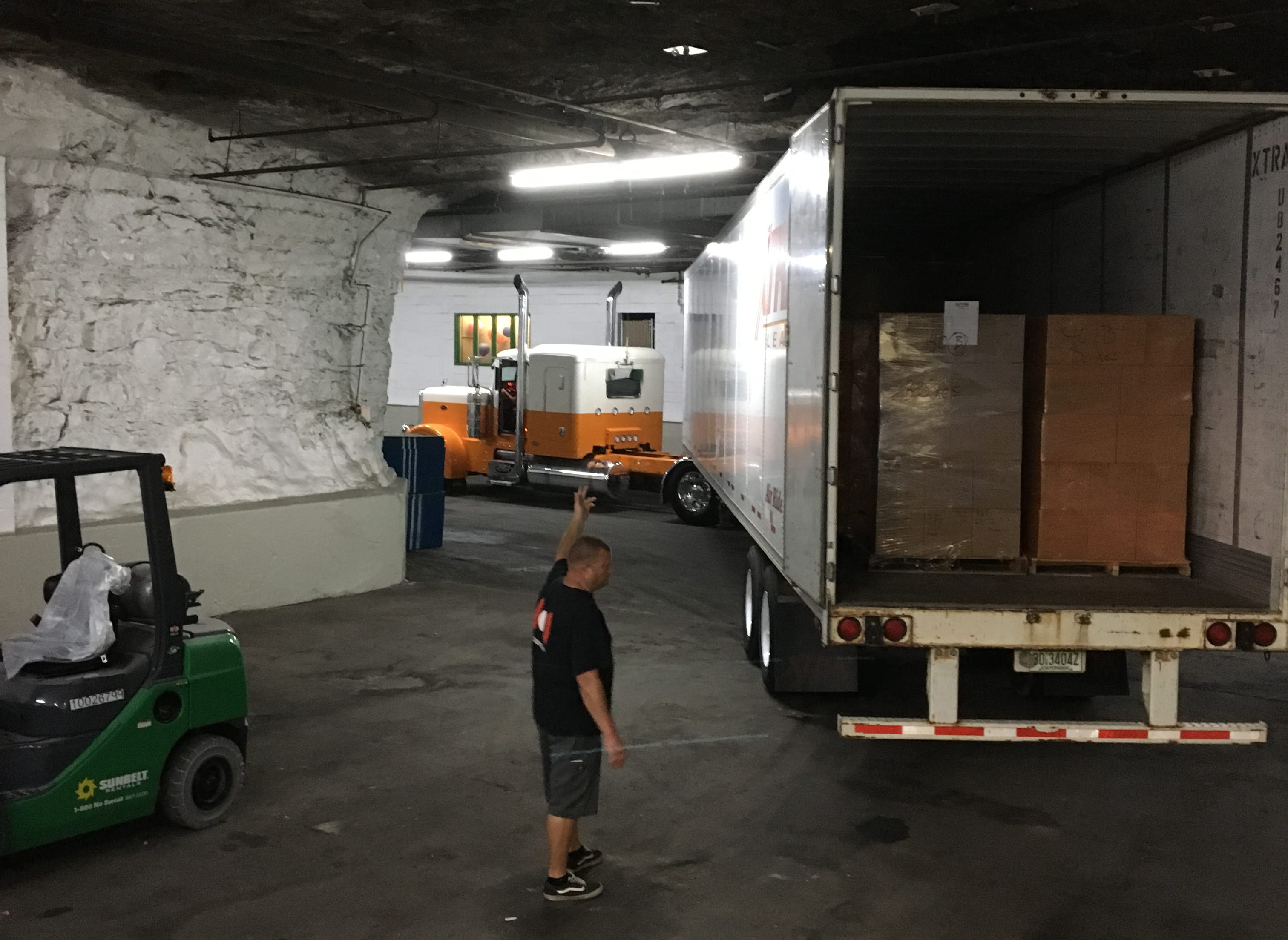 In an underground building with rough white stone walls, a man in a black t-shirt and shorts stands by the tail-end of an open semi trailer and directs the driver on backing up.