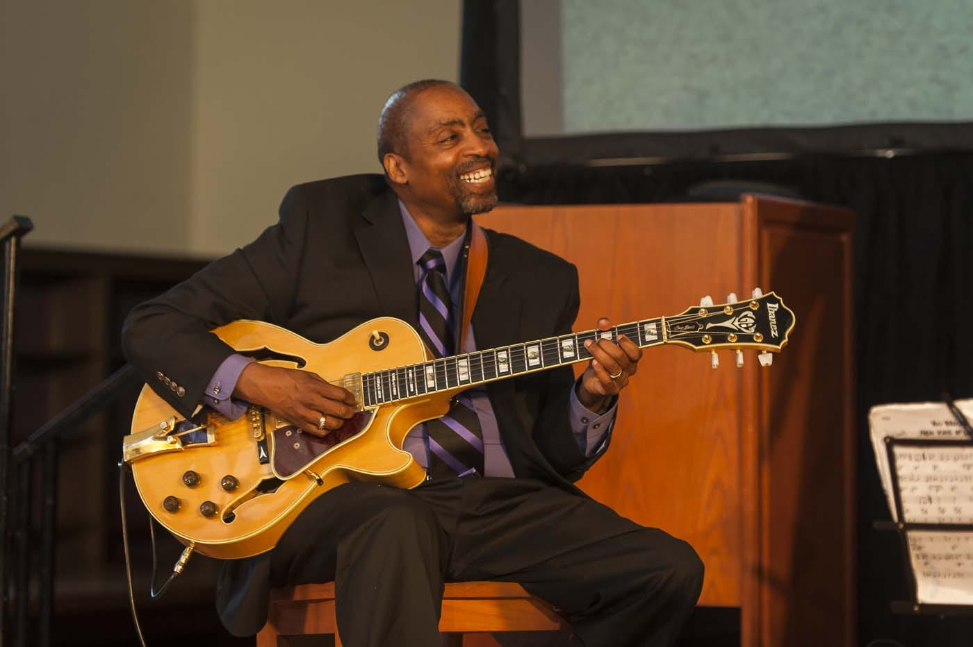 Dressed in a black suit, purple shirt, and purple and black tie, Dr. Goins smiles at his band mates while playing his guitar.