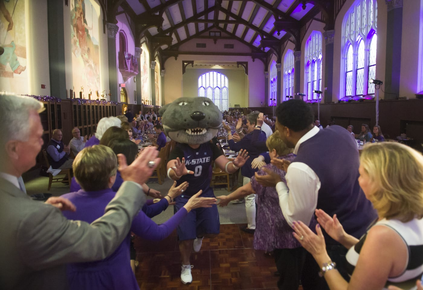 Willie the Wildcat gives high fives to a crowd of gala attendees gathered in the Great Room.