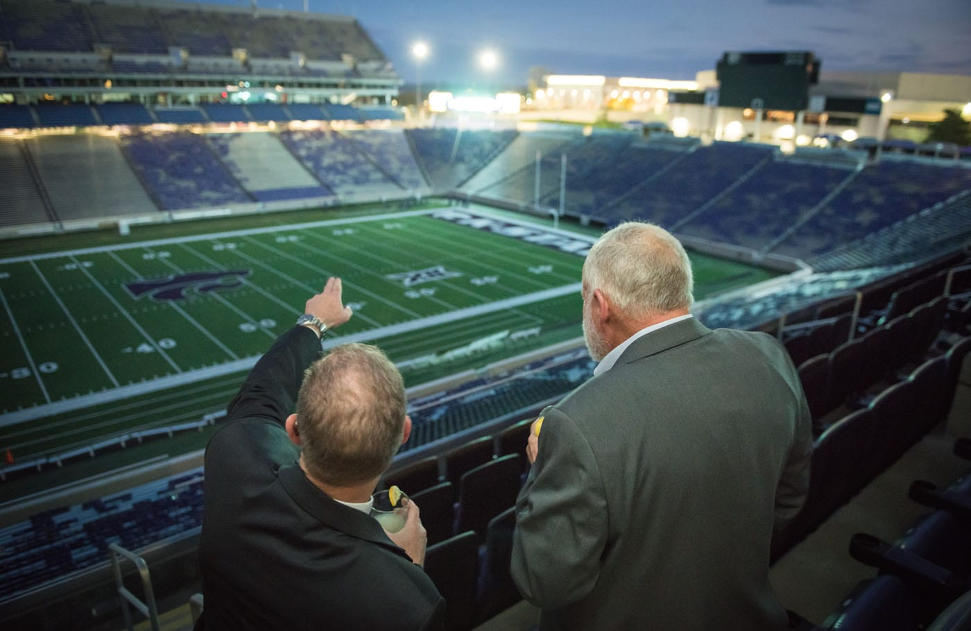 Two men face away from the camera as they look out over the football field in the Bill Snyder Family Stadium.