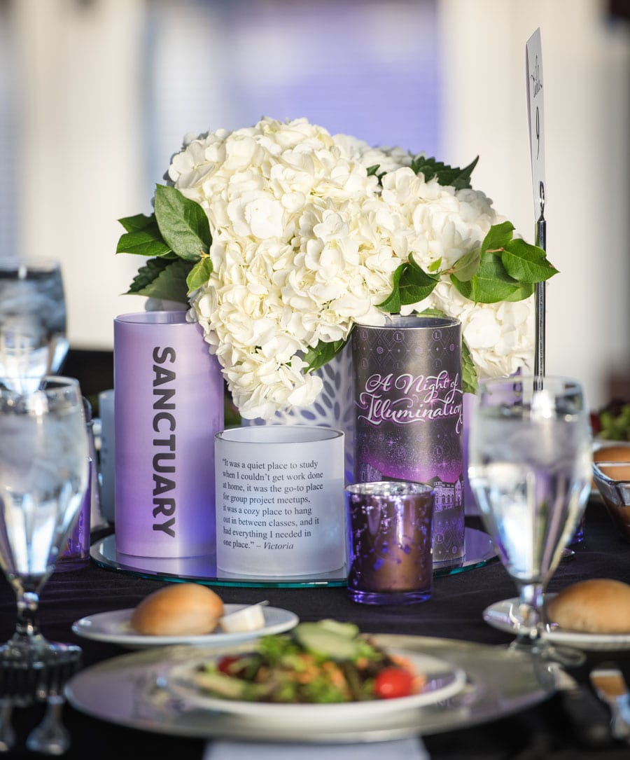 A close-up of the table arrangements featuring white hydrangeas and purple cylindrical vases and candles.