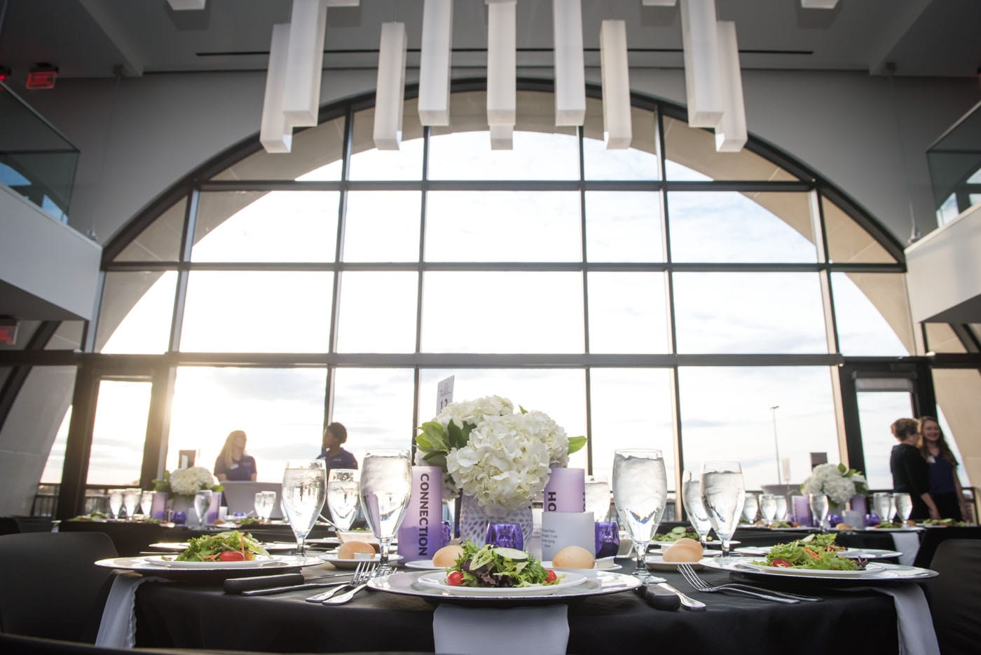 A round table covered in a black tablecloth, formal white place settings and a centerpiece of purple candles and white hydrangeas is framed by an enormous semi-circle window in the background that covers an entire wall.