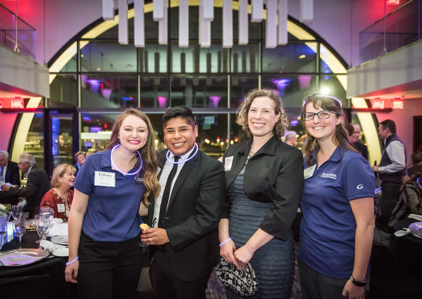 Four smiling gala attendees, including two students wearing purple student ambassador polo shirts, pose in the middle of the event space that glows with a soft purple light.
