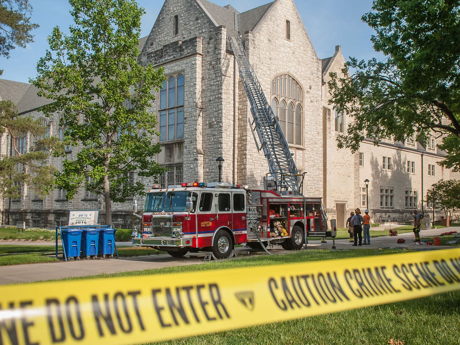 Yellow crime scene tape stretches across the foreground. A red fire truck with a metal ladder extends onto the roof of a limestone building.