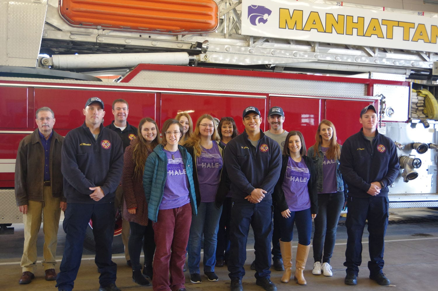 Librarians and firefighters gather for a photo in front of a firetruck.