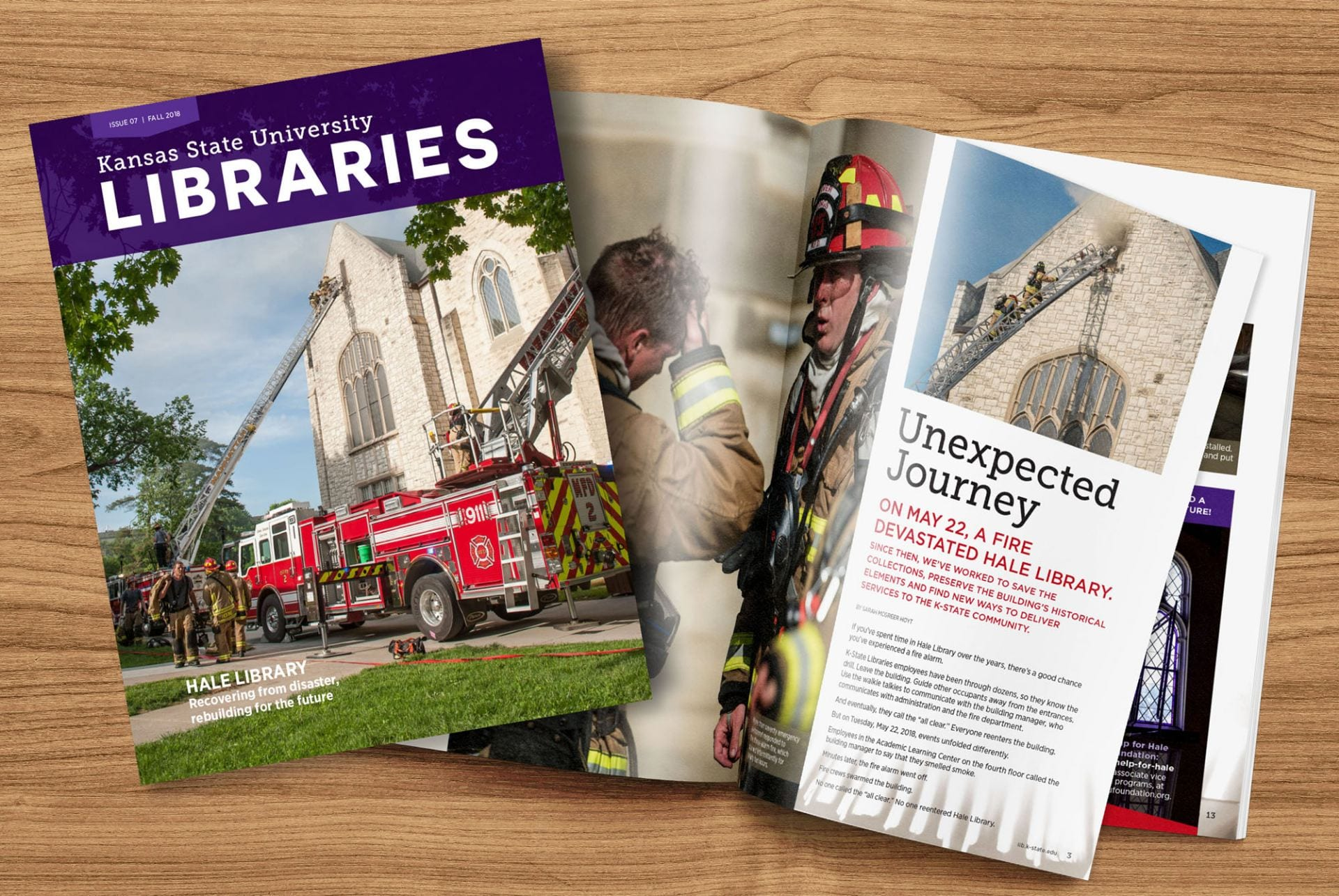 Two issues of K-State Libraries Magazine, one open and one closed, lie on a wooden surface. Both feature photos of firefighters outside Hale Library during a fire.