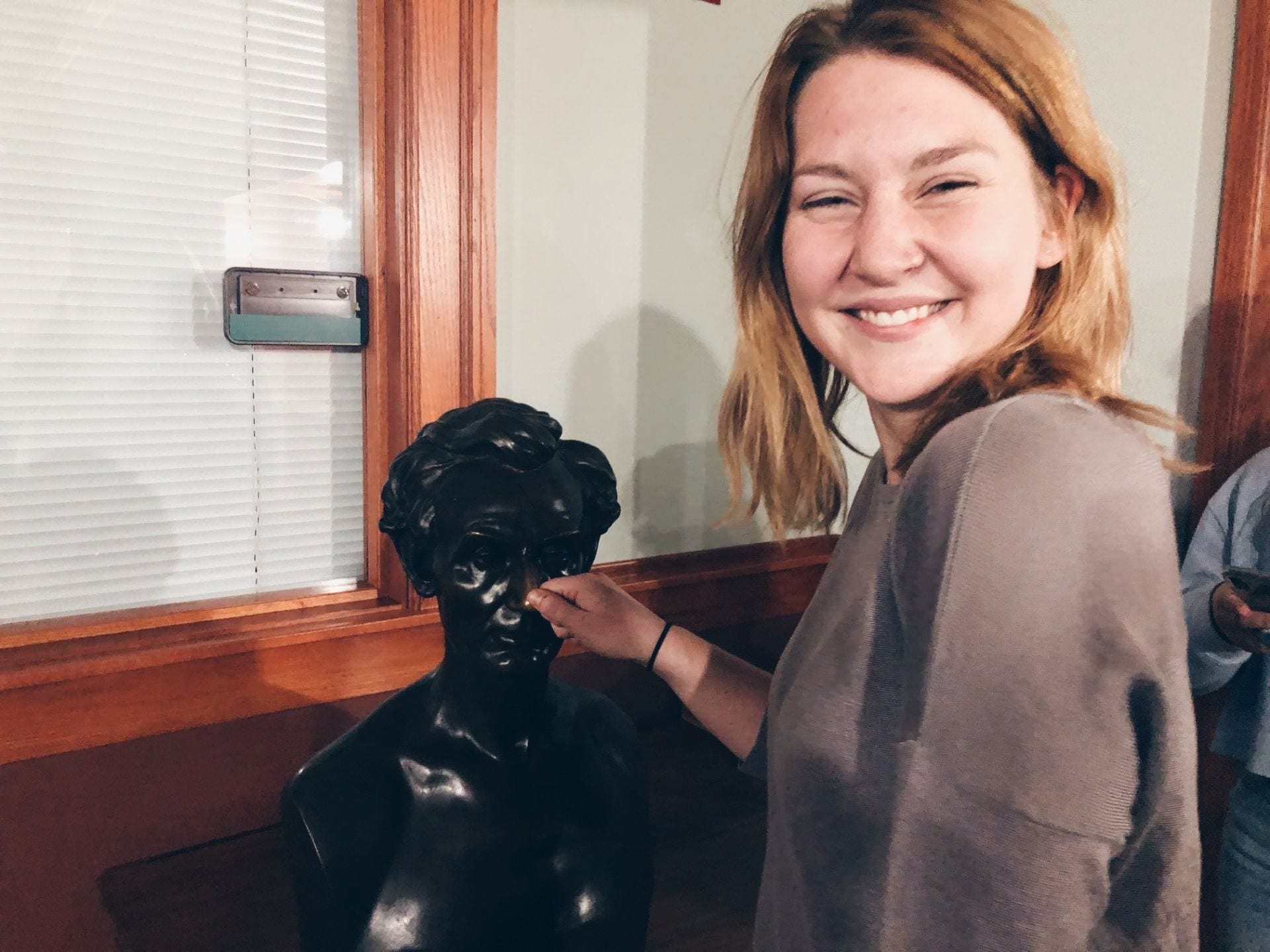 A student rubs the nose of a bust of Abraham Lincoln, one of a few items that still remain on the fifth floor.