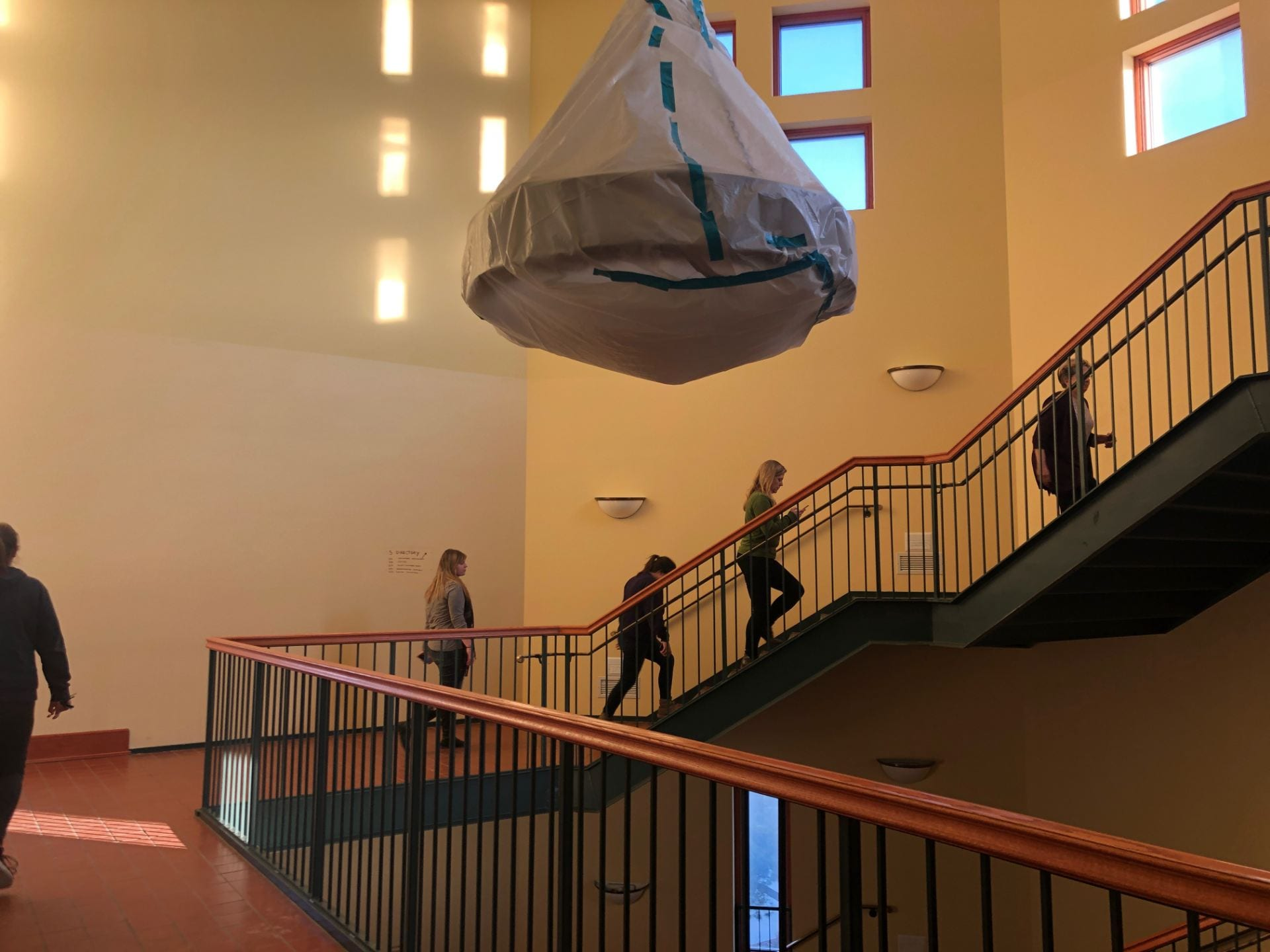 Students walk up the stairs to the fifth floor. A chandelier hangs covered in plastic.