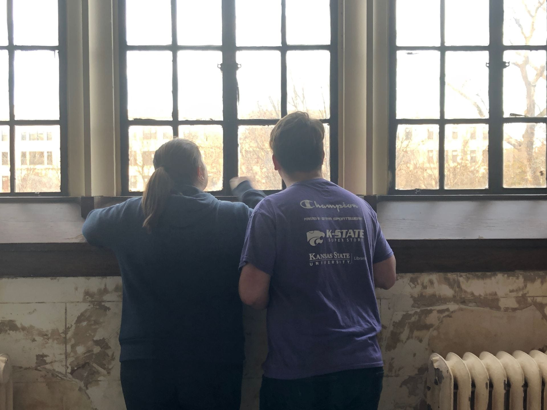 Two Library Student Ambassadors look at students walking below from the room that used to house iTAC.