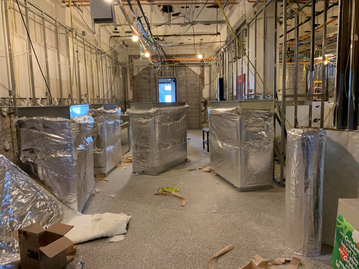 A room with a lot of exposed metal wall framing is filled with give large rectangular metal pieces of ductwork wrapped in metallic silver insulation.