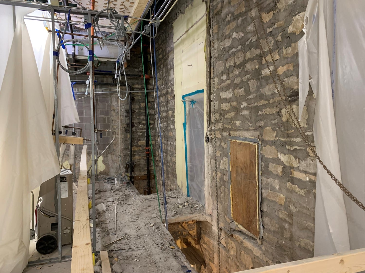A rough limestone wall is at right. Two narrow rectangular-shaped holes are cut in the floor in front of the wall. Dust and stone debris coats the rest of the floor.