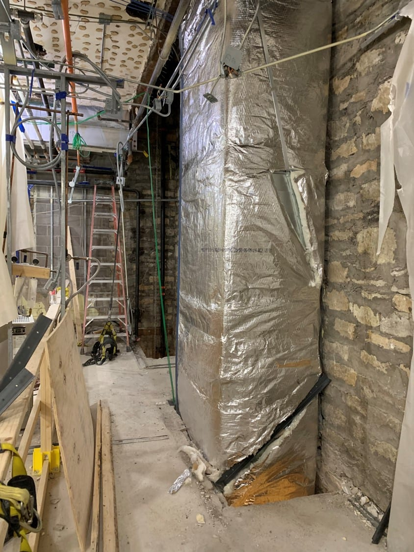 A length of metallic silver insulation-wrapped rectangular ductwork is installed in one of the chases in front of the limestone wall.