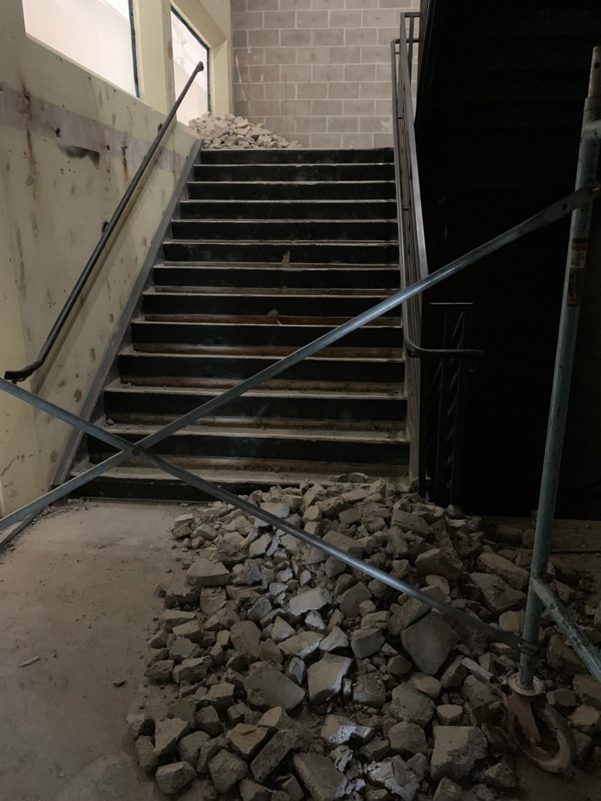 A pile of rubble sits at the base of a metal staircase.