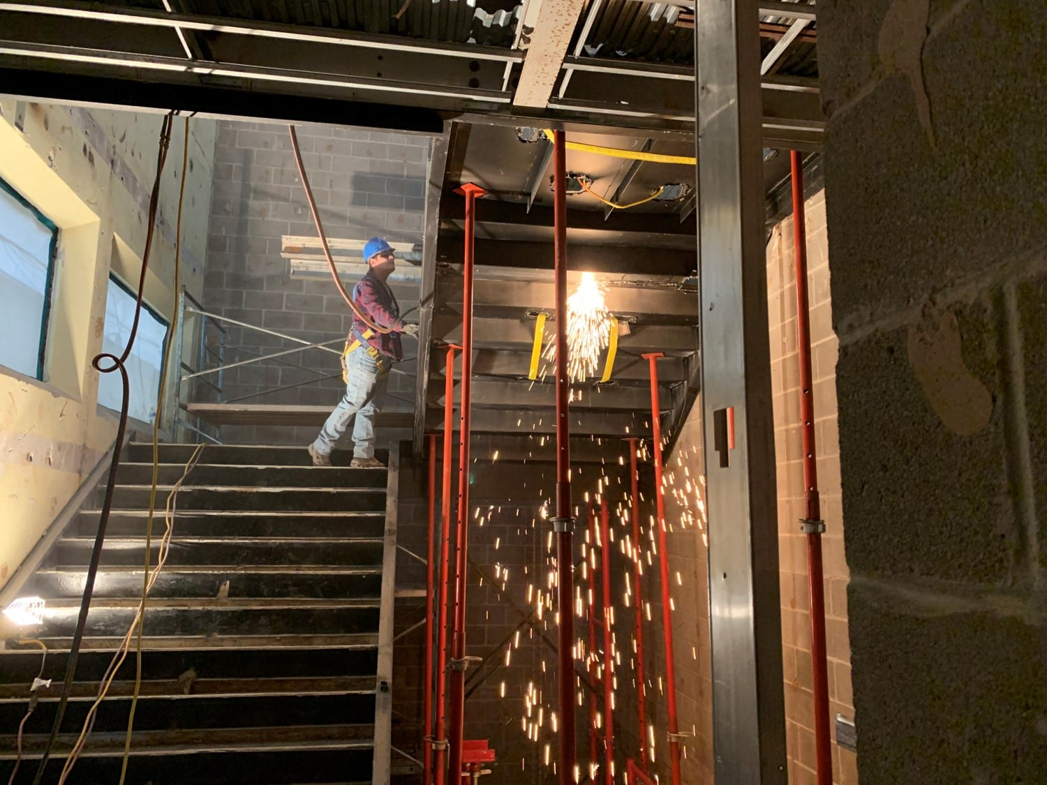 At the left, a worker in a blue hardhat stands on a staircase. A shower of sparks rains down from the next flight of stairs on the right.