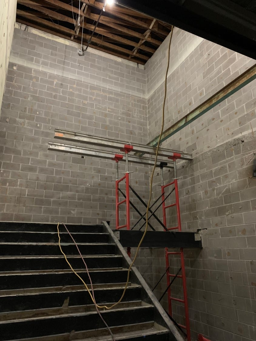 A stairwell made of concrete blocks stands nearly empty except for a small piece of metal stairway and a section of red scaffolding.
