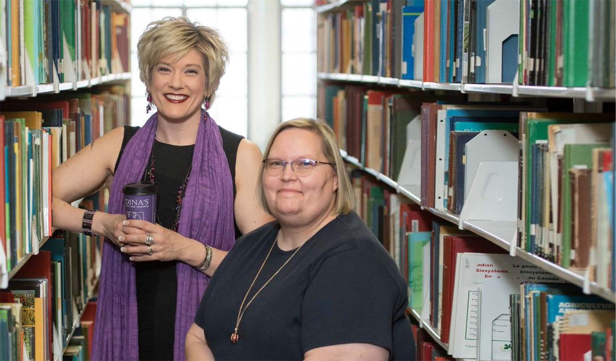 Two blonde, smiling women stand in an aisle with packed bookshelves on both sides.