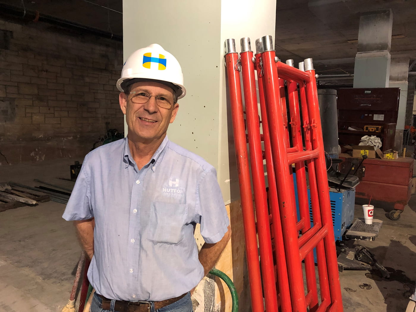 A man wearing glasses and a white hardhat stands on a construction site next to a stack of red metal pipes leaning on a concrete pillar.