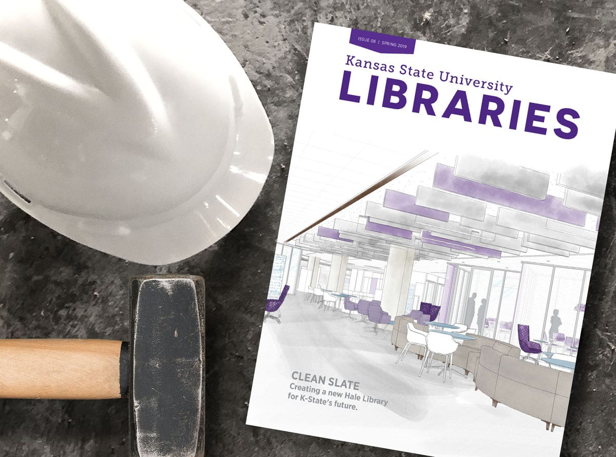 A white hard hat, a sledge hammer, and a copy of K-State Libraries Magazine sit on a concrete background.