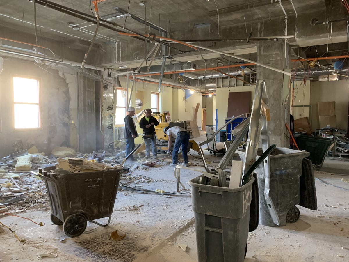 Three construction workers stand in a concrete room surrounded by debris on the floor in and several large trashcans.