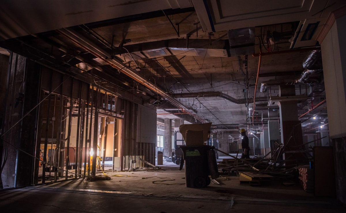 A light shines in a partially visible room at left, lighting up a concrete room filled with construction debris.