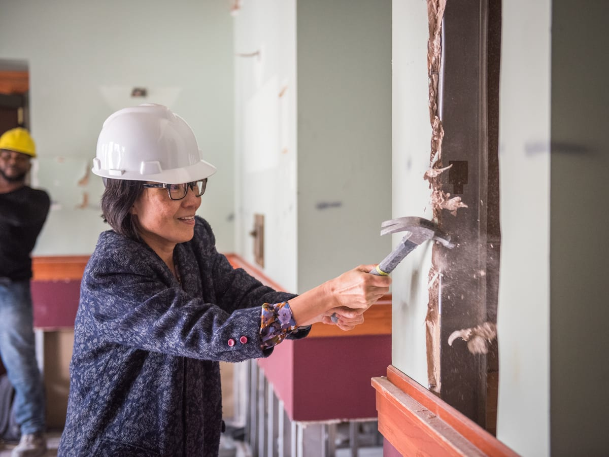 A petite dark-haired woman wearing glasses and a white hardhat knocks a small chunk of plaster out of the wall with a hammer.