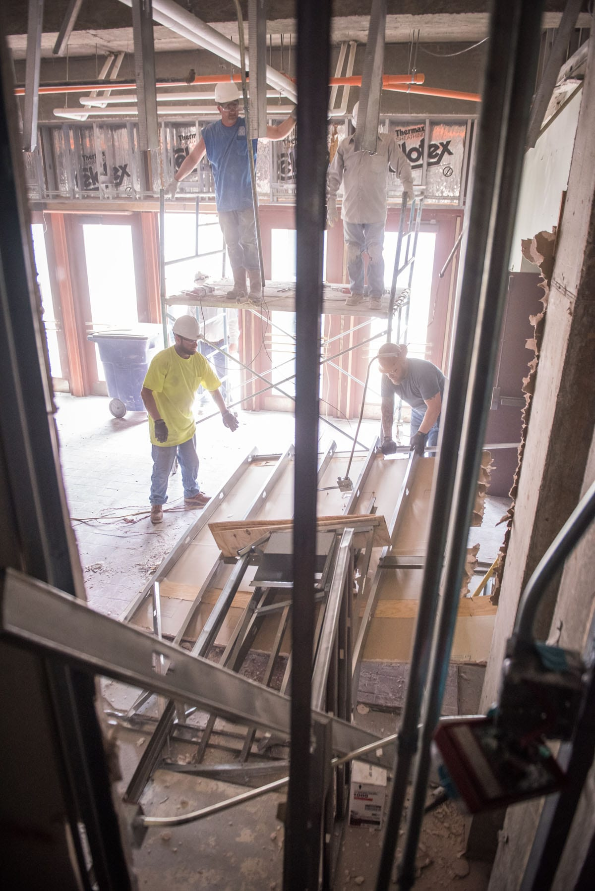 Four men, two on the ground and two elevated on scaffolding, are seen from behind pieces of metal framing lowering a piece of drywall to the floor.