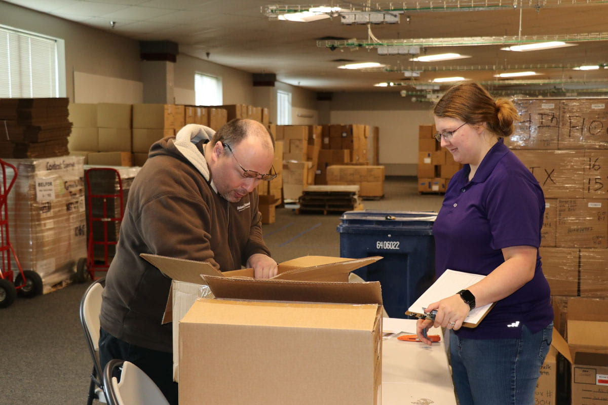 At left, a man in a brown hoodie reaches into a cardboard box sitting on a table in front of him. At right, a woman in a purple polo shirt holds a clipboard.
