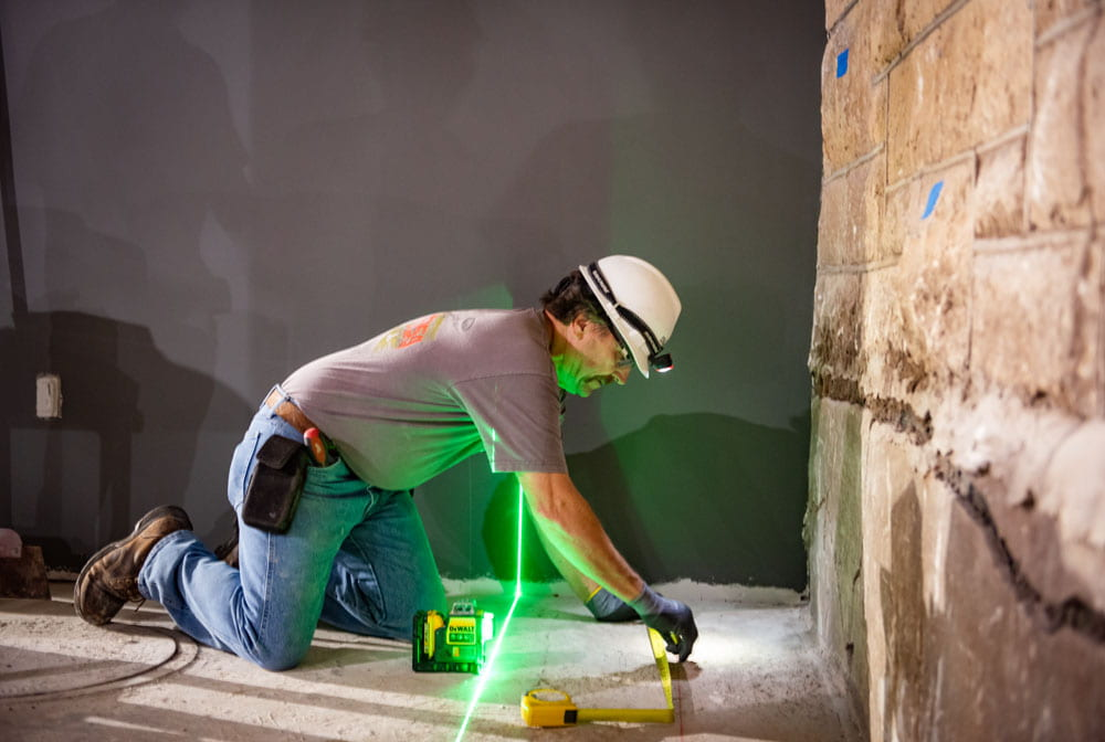 Man on all fours with green laser running length of photo