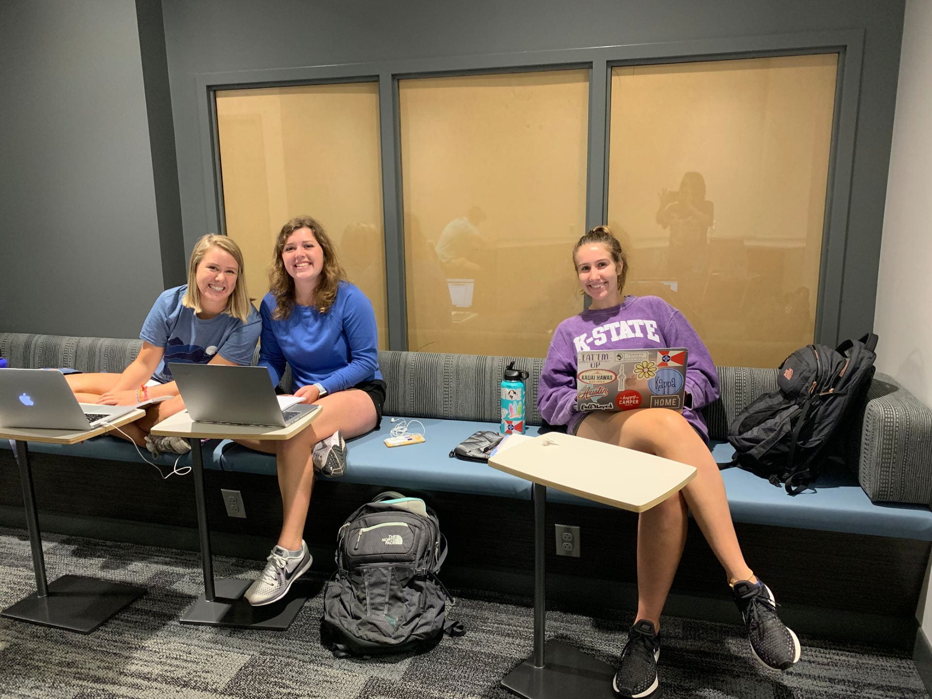 Three women sit on a blue padded bench with a gray wall and a window behind them.
