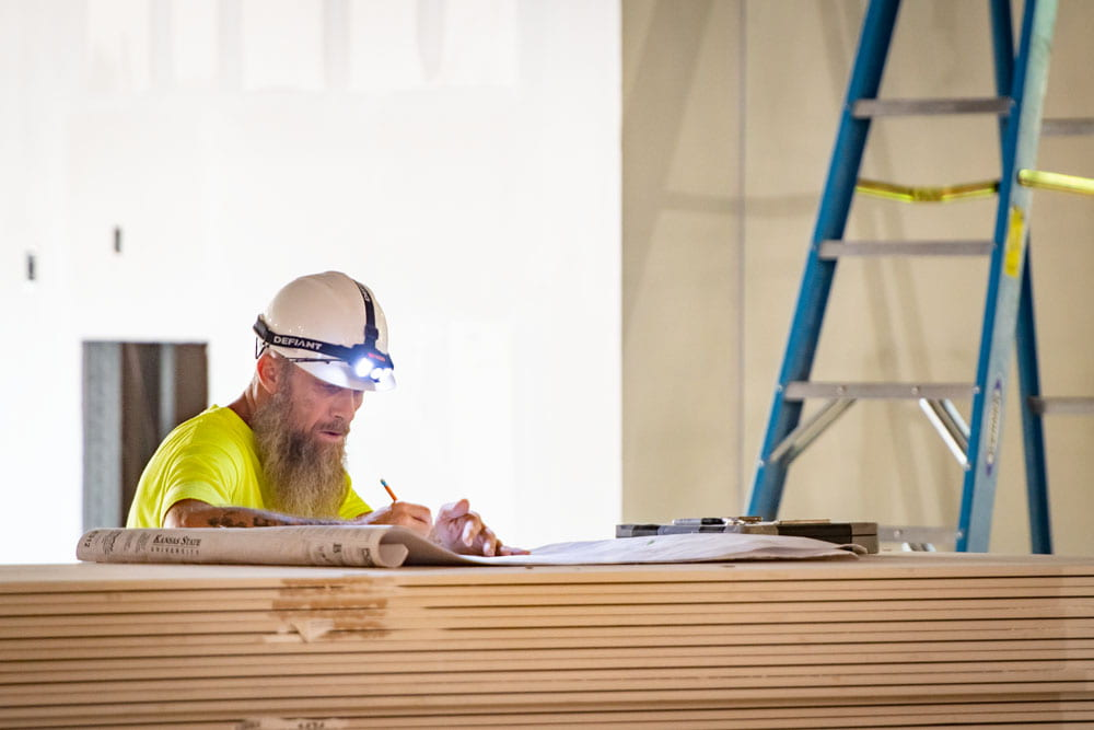 A man in a yellow hard hat writes on paper on stacks of wood