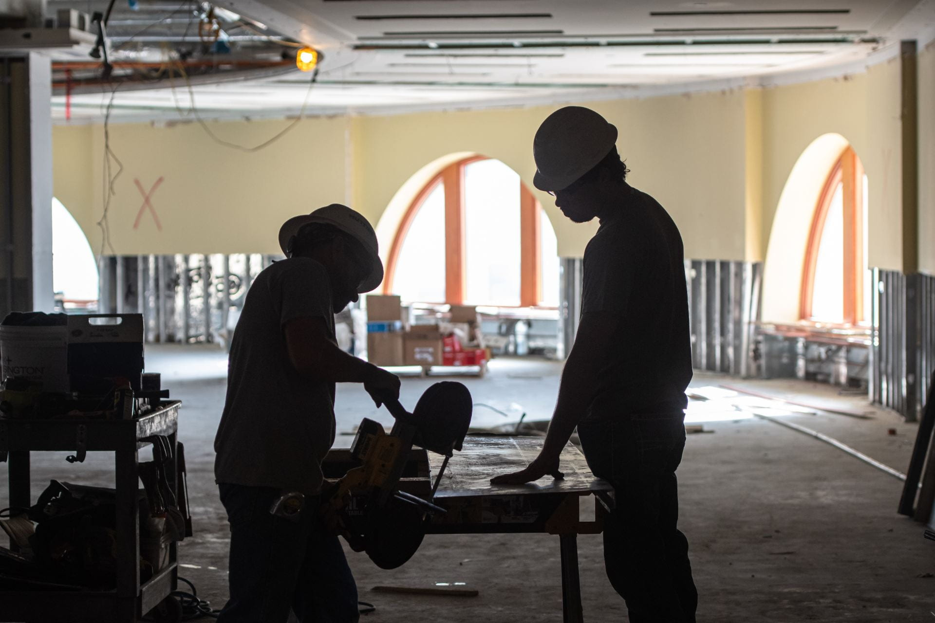 Two construction workers use a saw on the third floor of Hale Library.