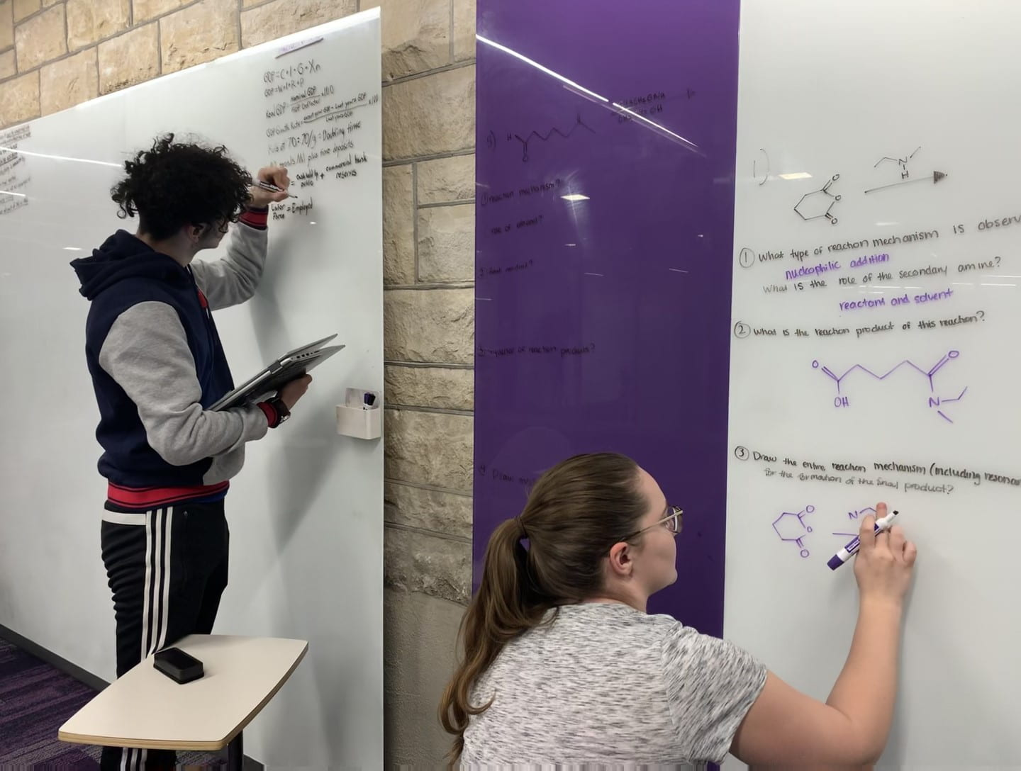 Two students write out information on white boards in Hale Library.
