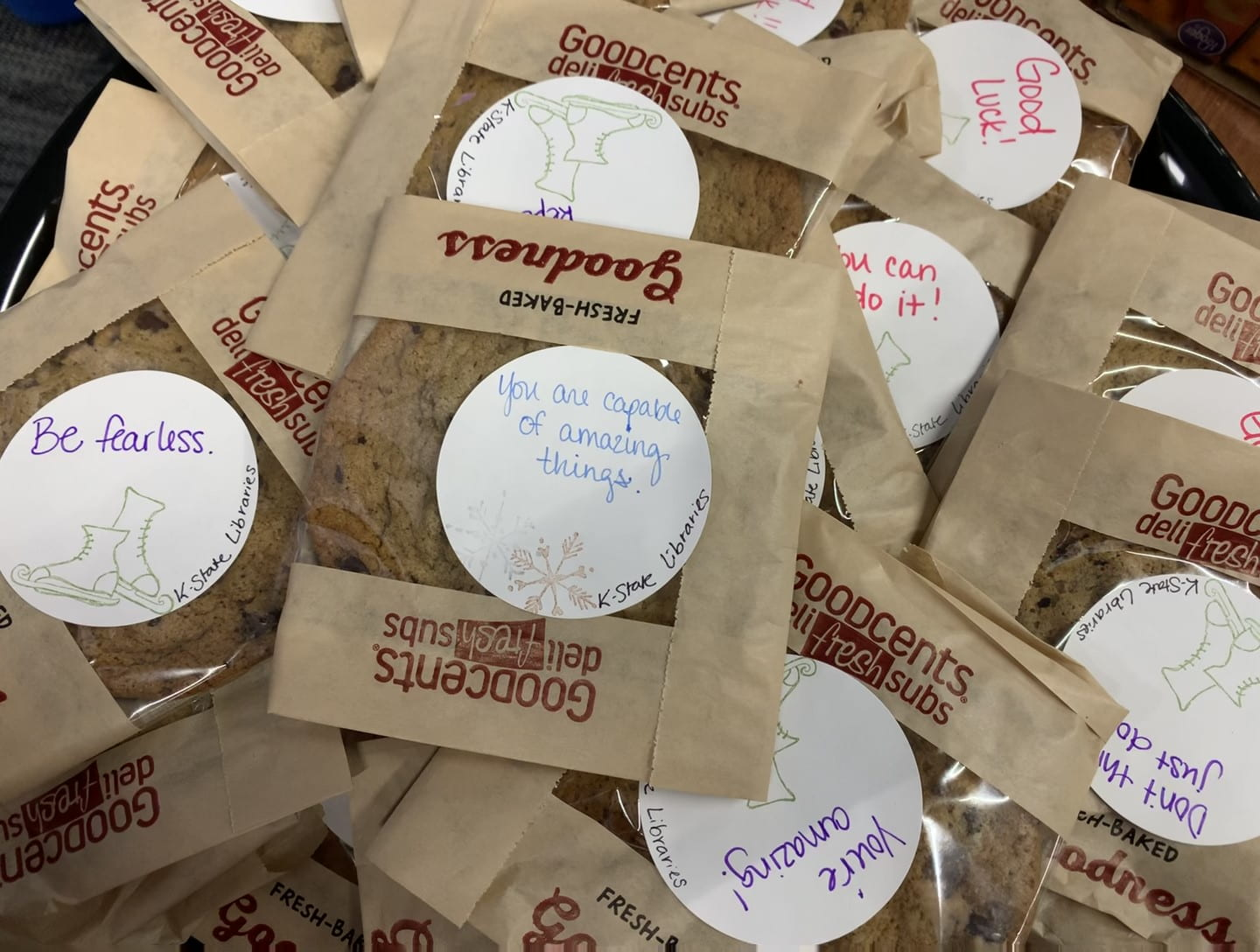 A pile of cookies with various encouraging phrases written on their wrappers.