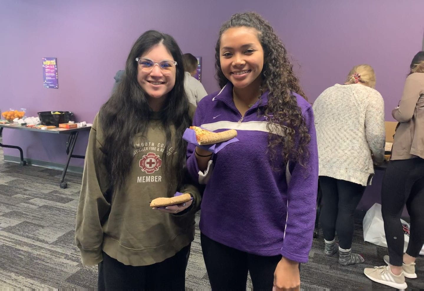 Two students smile holding pizza.