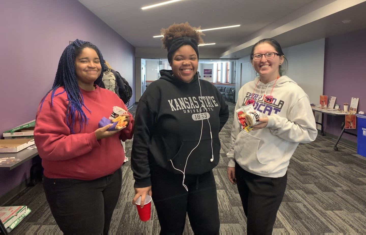Three students smile while holding food and drinks in Hale Library.