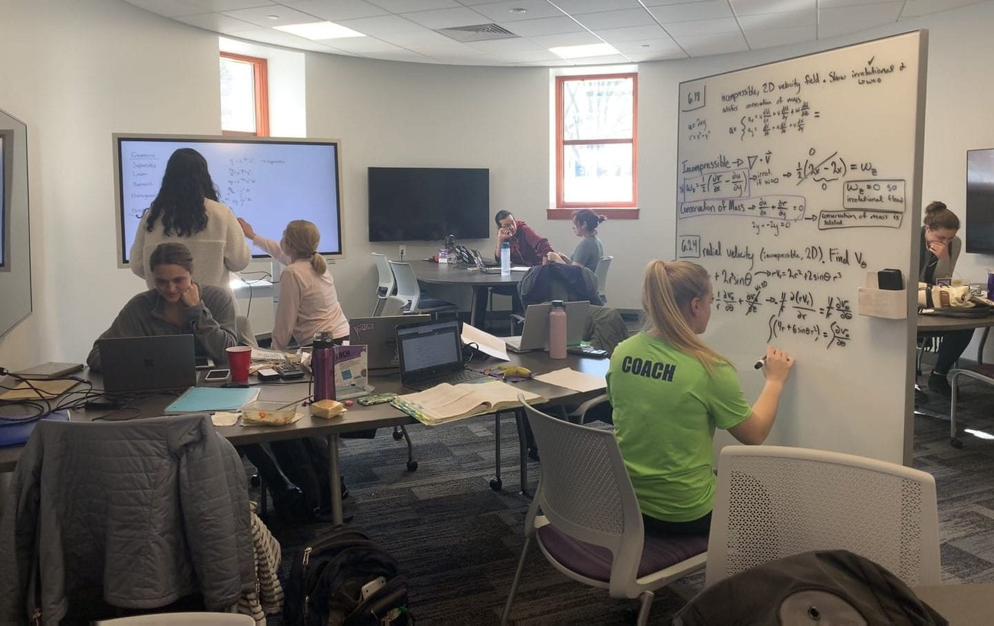 Several students study for exams using a white board, digital monitor, laptops and books.