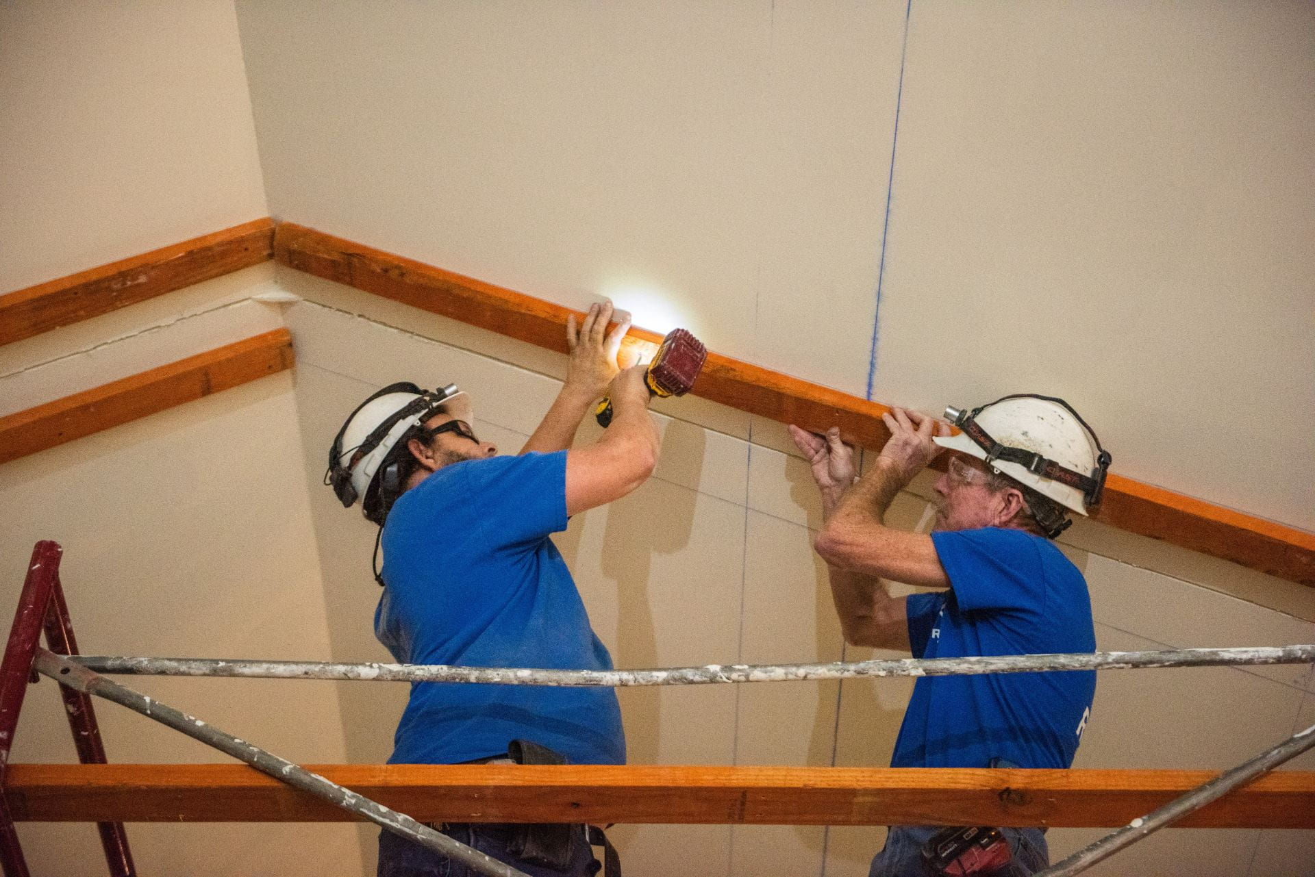 Two workers prep the ceiling for wood beams.