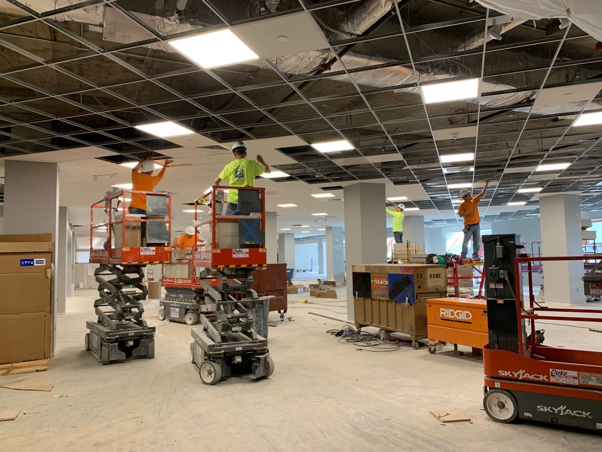 Several construction workers install ceiling tiles on Hale Library's second floor.