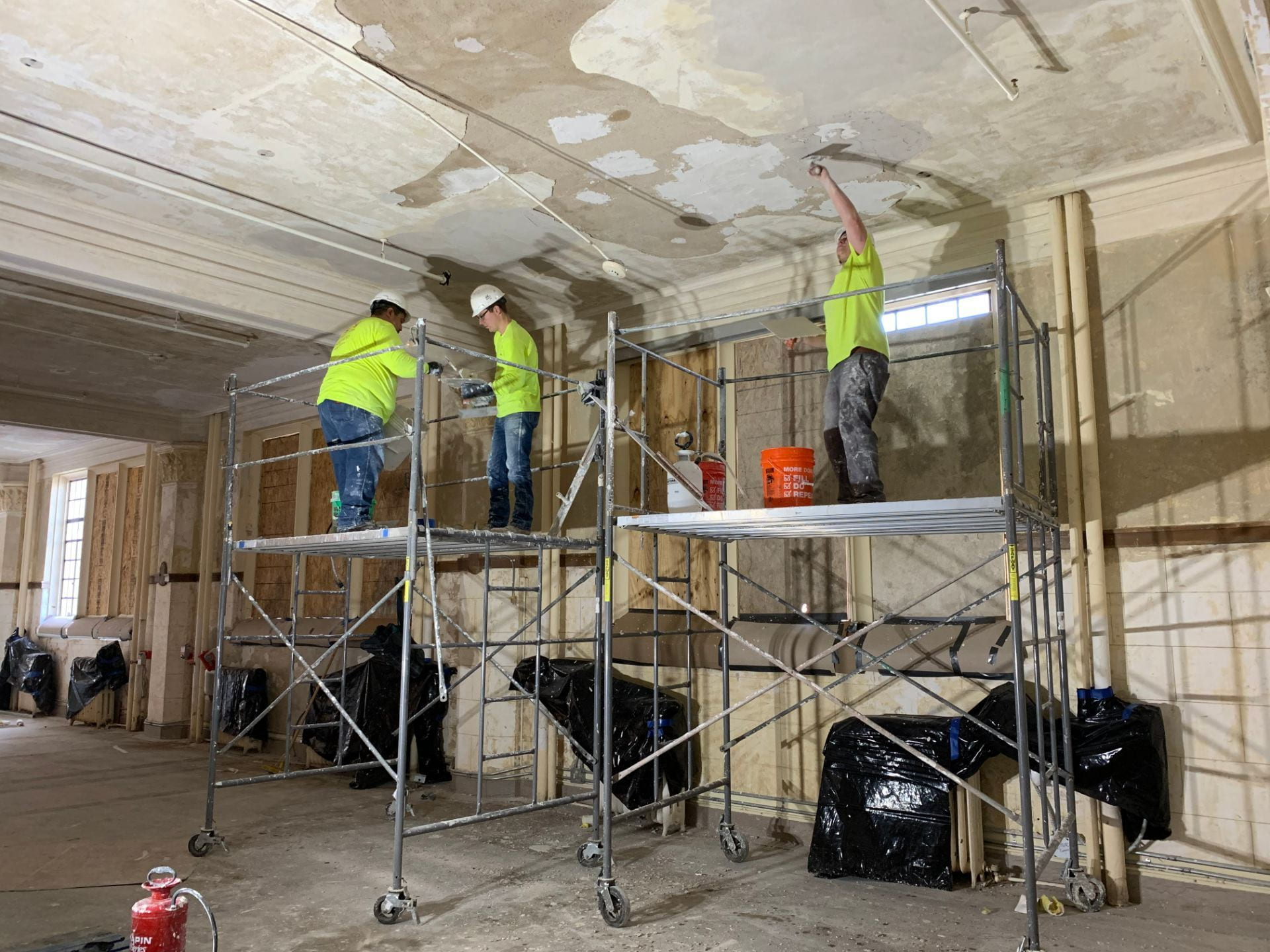 Three workers repair plaster on the ceiling in the historic portion of the building.