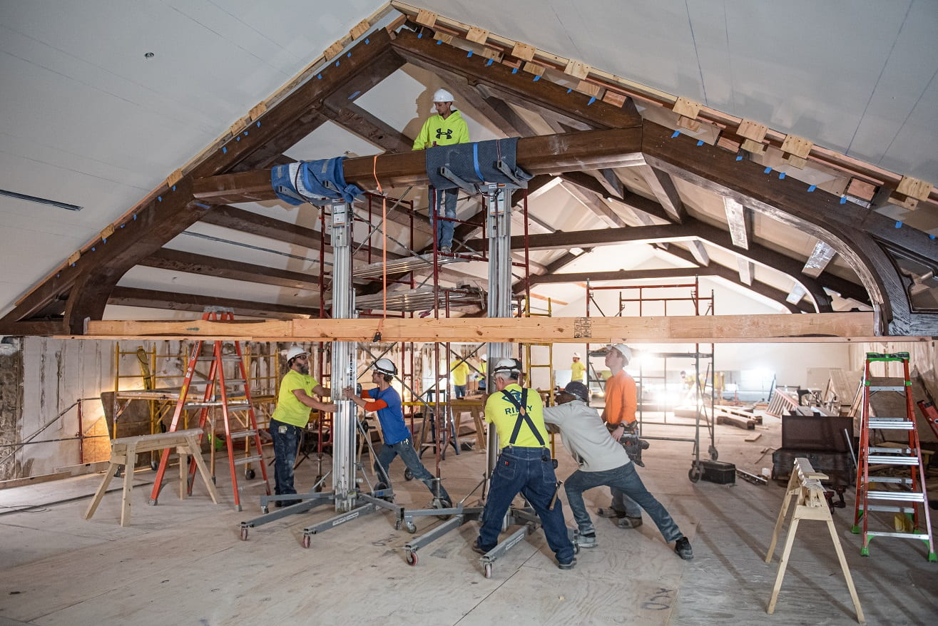 A picture of the construction crew pushing a wood center piece into place near the ceiling.
