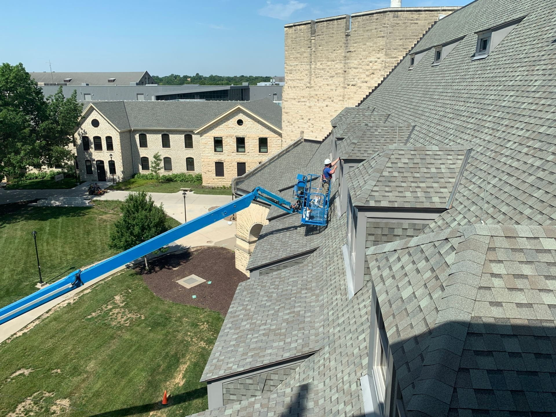 A picture of a crew member working on a lift outside the library.