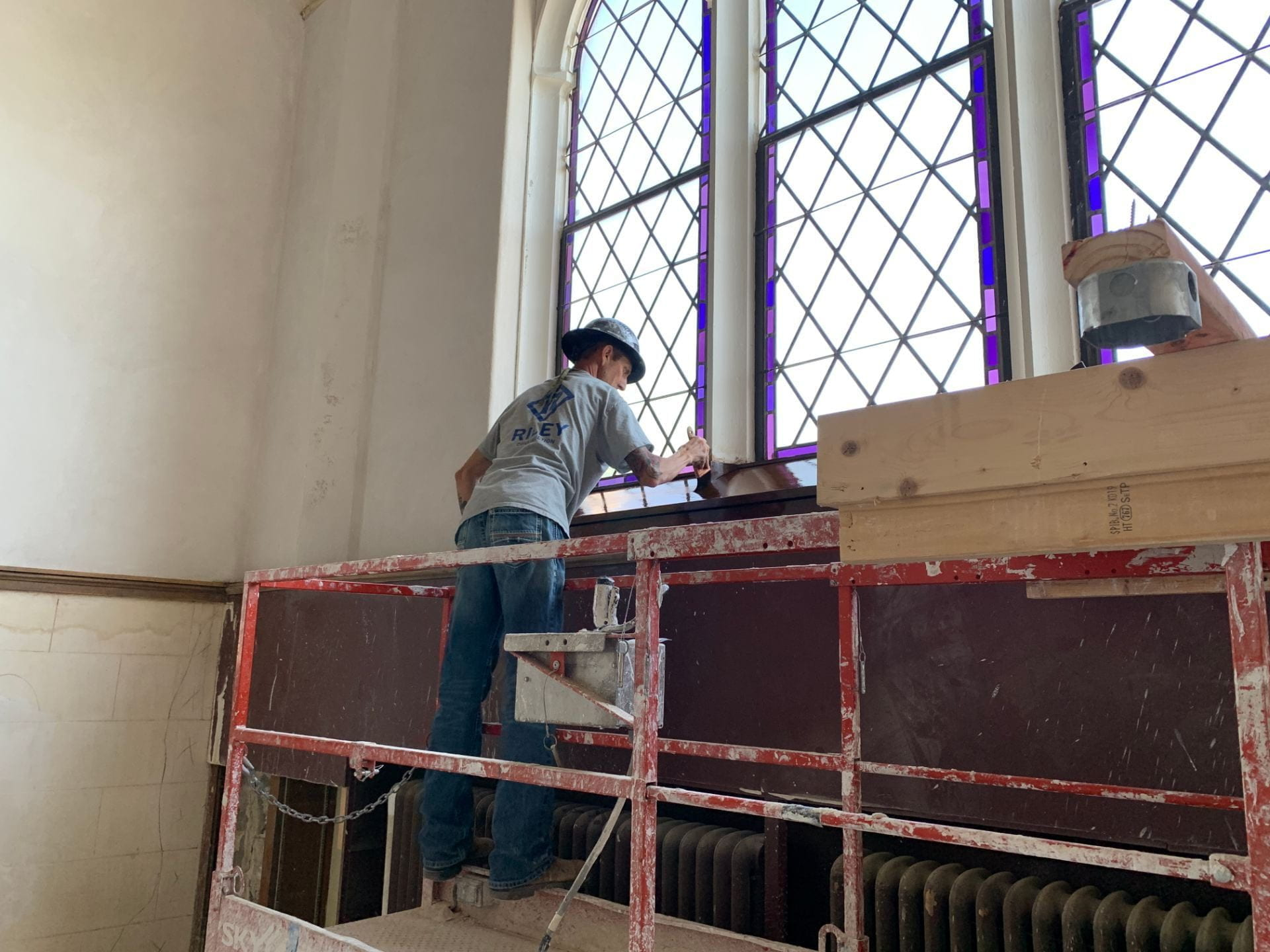 A picture of Brian Hawk varnishing wood near a Great Room window.