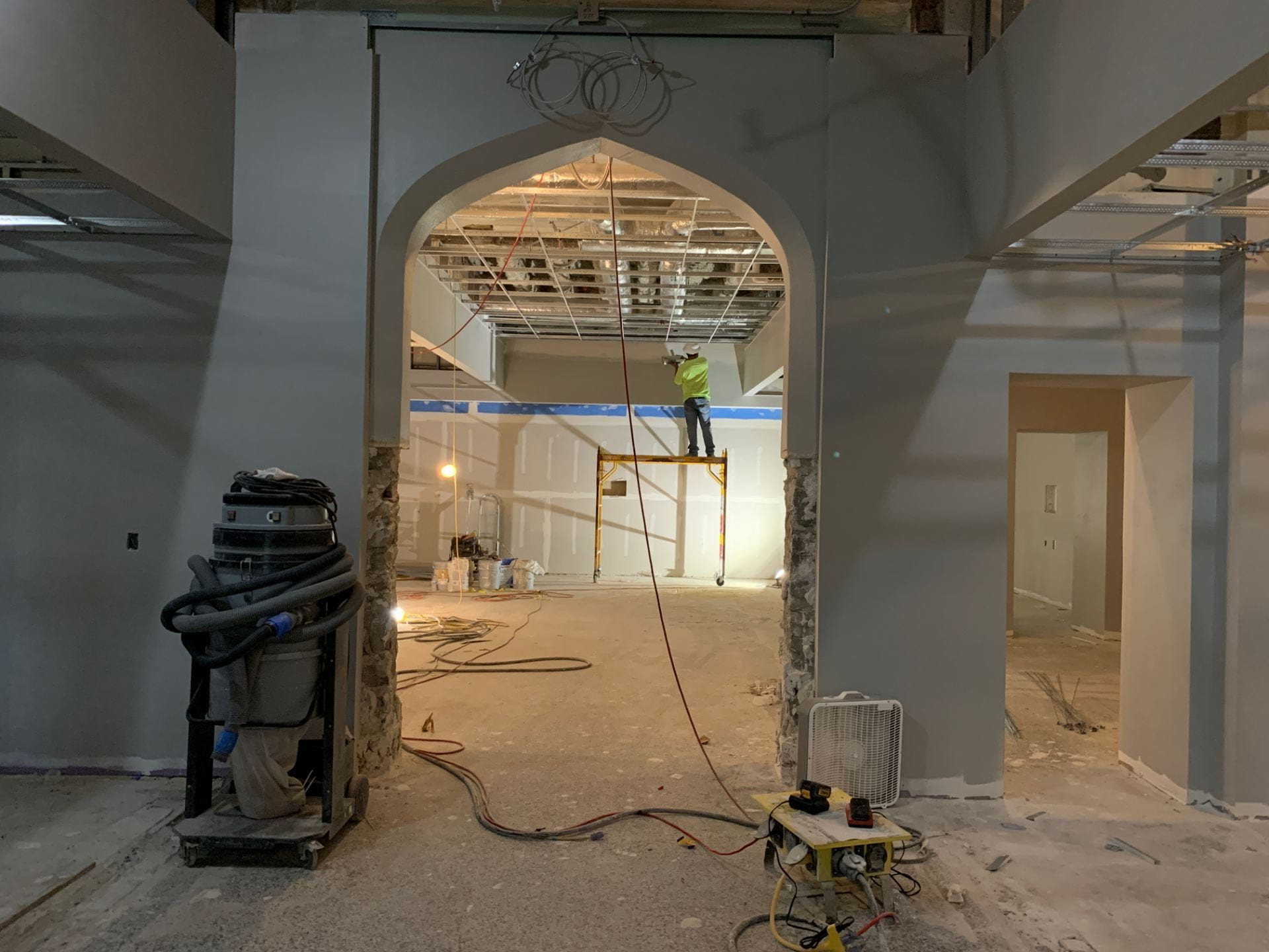 A construction worker is seen on the other side of an arched doorway.