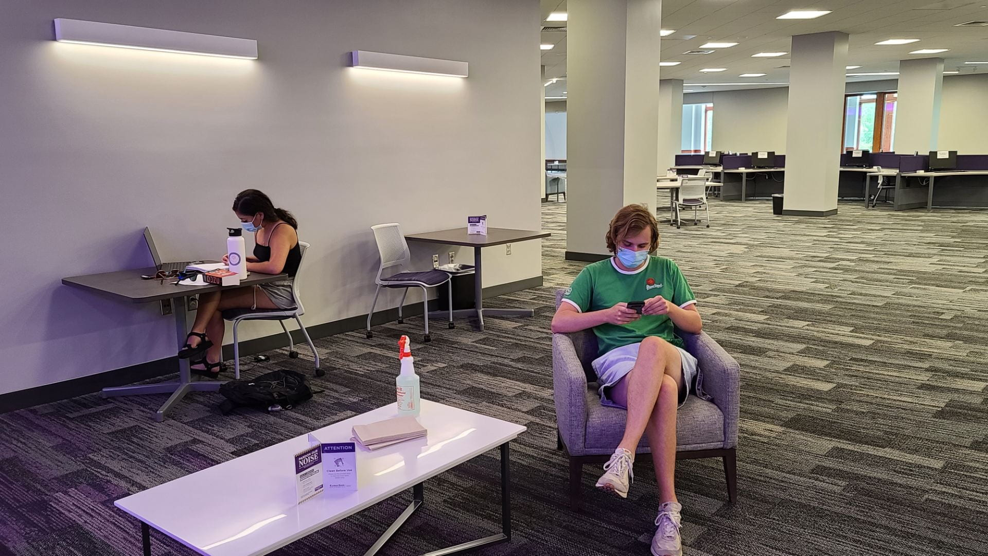 Two students are pictured sitting and studying in the library.